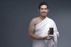 Portrait of asian muslim man in ihram dress holding smartphone Royalty Free Stock Photo