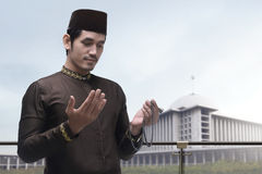 Portrait of asian muslim man raising hand and praying Stock Photos