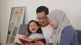 Asian muslim parent, mother, father and child are reading a book at home, happy excited expression, family education concept