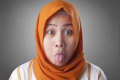 Muslim Woman With Tongue Out. Portrait of Asian muslim woman shows tongue out, mocking grimacing face expression indonesian malaysian arab shock surprised person royalty free stock images