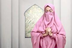 Portrait of asian muslim woman wearing niqab praying Stock Image