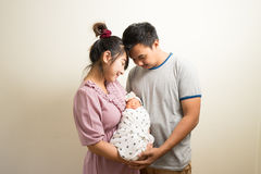 Portrait of Asian parents and six months old baby girl at home. Royalty Free Stock Photos