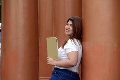 Portrait of Asian pretty smiley face fat woman pose standing and hold a booklet in hand. Royalty Free Stock Photography