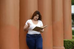 Portrait of Asian pretty fat woman pose and thinking at a pole. Royalty Free Stock Photos