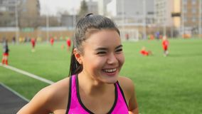 Portrait of asian runner girl laughing on stadium before the start. Portrait of asian runner girl laughing on stadium before the start in campus. Front view stock video footage
