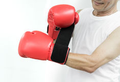 Portrait of Asian senior fighter man putting his hands into red. Boxing gloves on white background Royalty Free Stock Photos