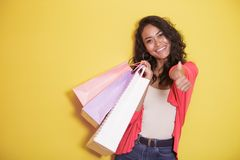 Asian shopaholic smiling while giving thumbs up. Portrait of asian shopaholic smiling while giving thumbs up on yellow background Stock Photography
