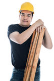 Portrait of asian smiling carpenter holding wood planks. Royalty Free Stock Image