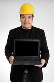 Portrait of asian smiling holding laptop with safety helmet Stock Image