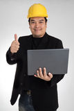 Portrait of asian smiling holding laptop with safety helmet Royalty Free Stock Photos
