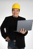 Portrait of asian smiling holding laptop with safety helmet Royalty Free Stock Photography