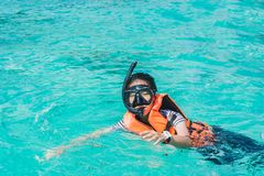 Portrait of an asian snorkeling girl with mask swiming on the se stock image