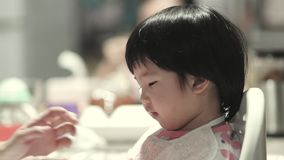 Portrait of asian toddler baby girl eating snack with her mom helping teaching her to use fork by herself with dining table atmosp stock video footage