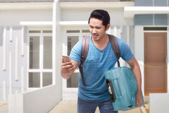 Portrait of asian traveler man running carrying suitcase Stock Photos
