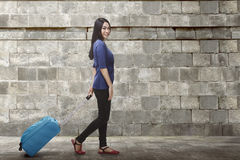 Portrait of asian traveler woman carrying luggage walking Royalty Free Stock Image
