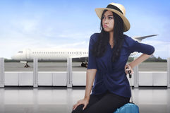Portrait of asian traveler woman with unhappy face sitting on su Royalty Free Stock Image