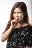 Portrait of Asian woman in Black sequin shirt nip her finger Royalty Free Stock Image