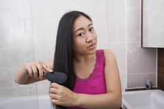 Portrait of Asian woman brushing her hair in bathroom Stock Photography