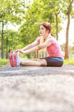 A portrait of a asian woman doing stretching exercise. Before or after jogging in the city park on the morning royalty free stock image