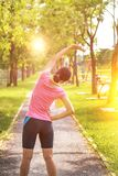 A portrait of a asian woman doing stretching exercise. Before or after jogging in the city park on the morning stock photography