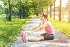 A portrait of a asian woman doing stretching exercise. Before or after jogging in the city park on the morning Stock Image