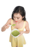 Portrait of asian woman eating/holding a plate of green vegetabl Royalty Free Stock Image