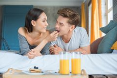 Portrait of asian woman feeding caucasian boyfriend. With breakfast in bed at home royalty free stock photo