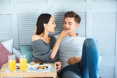Portrait of asian woman feeding caucasian boyfriend. With breakfast in bed at home royalty free stock photos