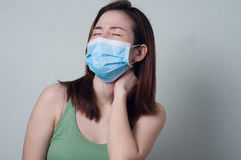 Portrait of Asian woman in a green shirt wearing a mask are fee. Asian Beauty woman in a green shirt wearing a mask are feeling sore neck royalty free stock photo