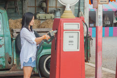 Portrait Asian woman holding red petrol pump nozzle with retro car background. Stock Photos