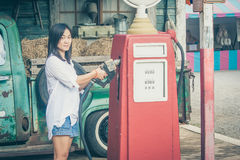 Portrait Asian woman holding red petrol pump nozzle with retro car background at countryside. Stock Photos