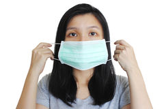 Portrait of Asian woman putting on medical mask on white background. Portrait of Asian woman putting on green medical mask on white background Stock Photos