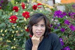 Portrait Asian woman With red flowers And purple flowers royalty free stock photography