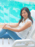 Portrait of an Asian woman relaxing on a pool chair Stock Image