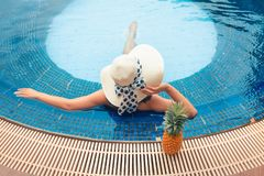 Portrait of asian woman relaxing in swimming pool and sunbathing royalty free stock photo