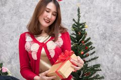 Portrait of asian woman sit near christmas tree at home. girl wi Royalty Free Stock Photo