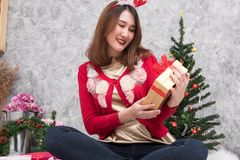 Portrait of asian woman sit near christmas tree at home. girl wi Royalty Free Stock Images
