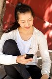 Asian woman sitting outside and reading a text message on mobile phone Stock Photo