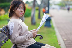 Portrait Asian woman sitting reading a document. Royalty Free Stock Image