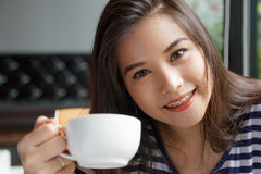Portrait of asian woman smiling and holding  cup of coffee Stock Photos