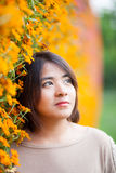 Portrait Asian woman standing near yellow flowers. Stock Image