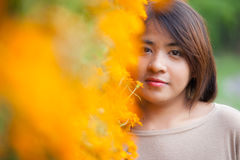 Portrait Asian woman standing near yellow flowers. Royalty Free Stock Photos