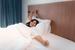 Portrait of asian woman waking up in bedroom and stretching her. Arms in the morning Royalty Free Stock Photography