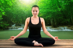 Portrait of asian woman wearing black body suit sitting in yoga. Meditation position with beautiful natural scene of water falls Stock Photos