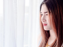 Portrait of Asian woman in white vest, expressing the idea of broken heart and sadness. hopeless and await, concept. White tone Royalty Free Stock Images