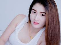 Portrait of Asian woman in white vest, on her bed, expressing the idea of broken heart and sadness. hopeless and await, concept. White tone Royalty Free Stock Images