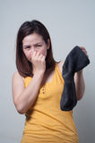 Portrait of Asian woman in a yellow dress smelling socks foul. Stock Photography