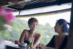 Portrait of 2 asian women chatting, drinking & smiling at beach bar in summer stock images