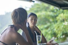 Portrait of 2 asian women chatting, drinking & smiling at beach bar in summer. Ko samui, thailand royalty free stock photography
