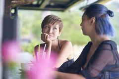 Portrait of 2 asian women chatting, drinking & smiling at beach bar in summer royalty free stock image